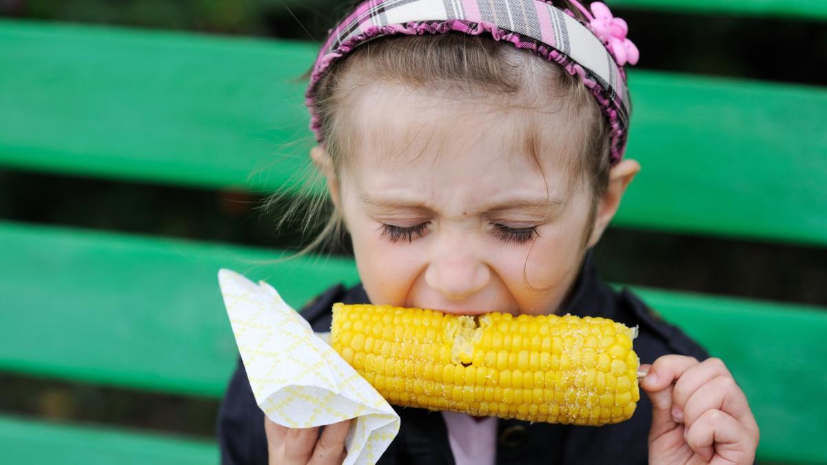 Dziewczynka je kukurydzę.