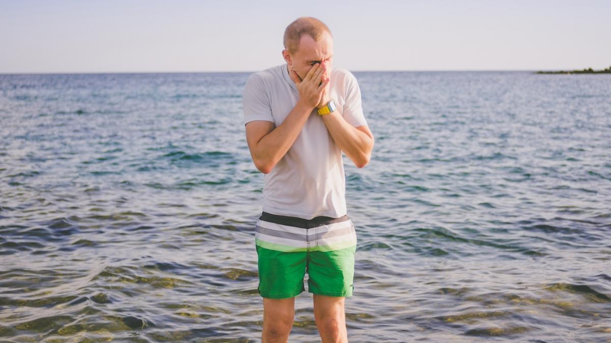 Mężczyzna zakrywający twarz nad brzegiem morza