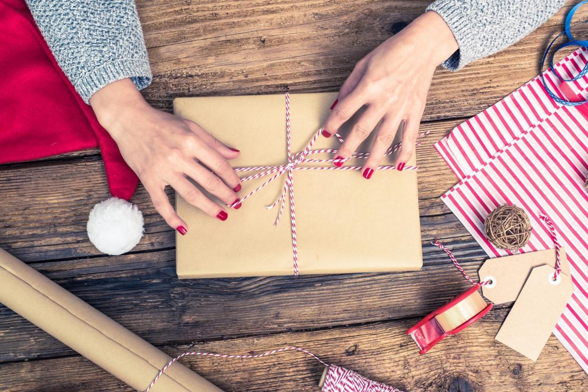 Widok na drewniany blat. Na blacie książka zapakowana na świąteczny prezent. Obok akcesoria do pakowania. Kokardę na prezencie zawiązują kobiece dłonie.