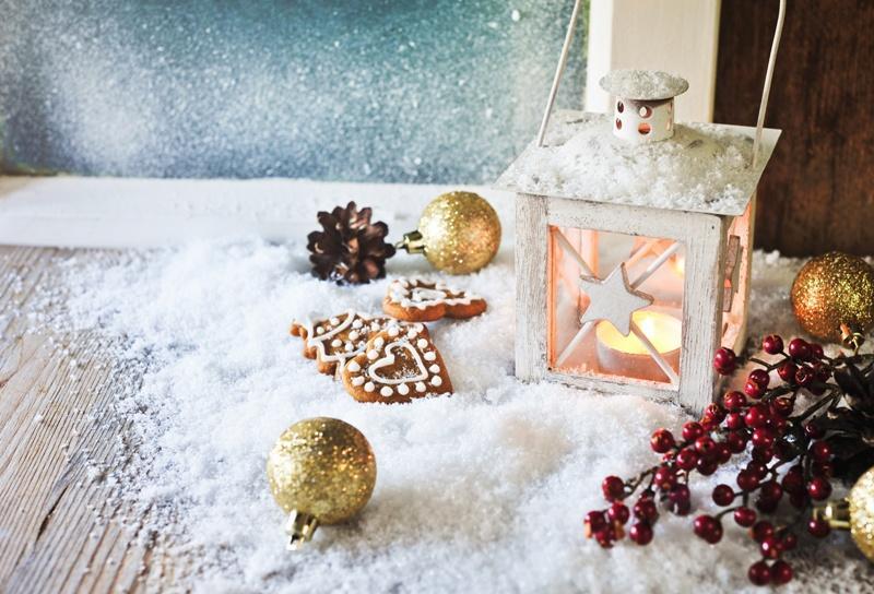 Biały lampion w śniegu z piernikami i złotymi bombkami