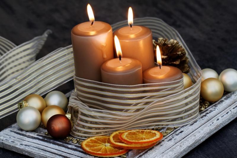 Świeczki ze wstążką, bombkami i suszonymi plastrami pomarańczy