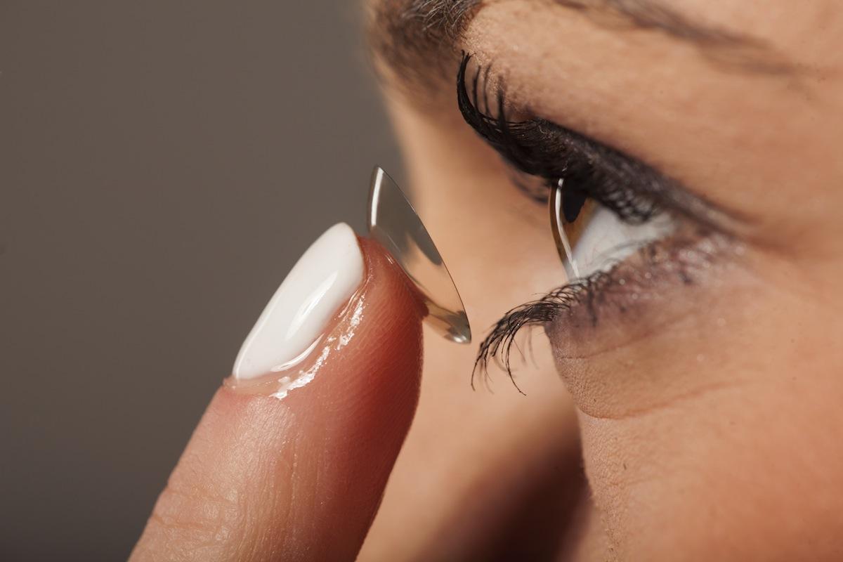 kobieta wkłada sobie soczewkę kontaktową