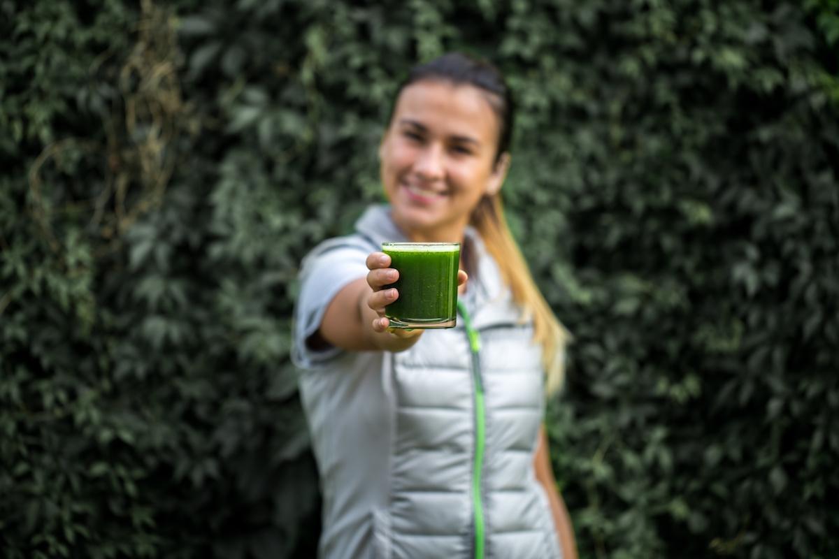 niewyrażnie widoczna kobieta trzyma w wyciągniętej ręce szklankę z zielonym koktajlem
