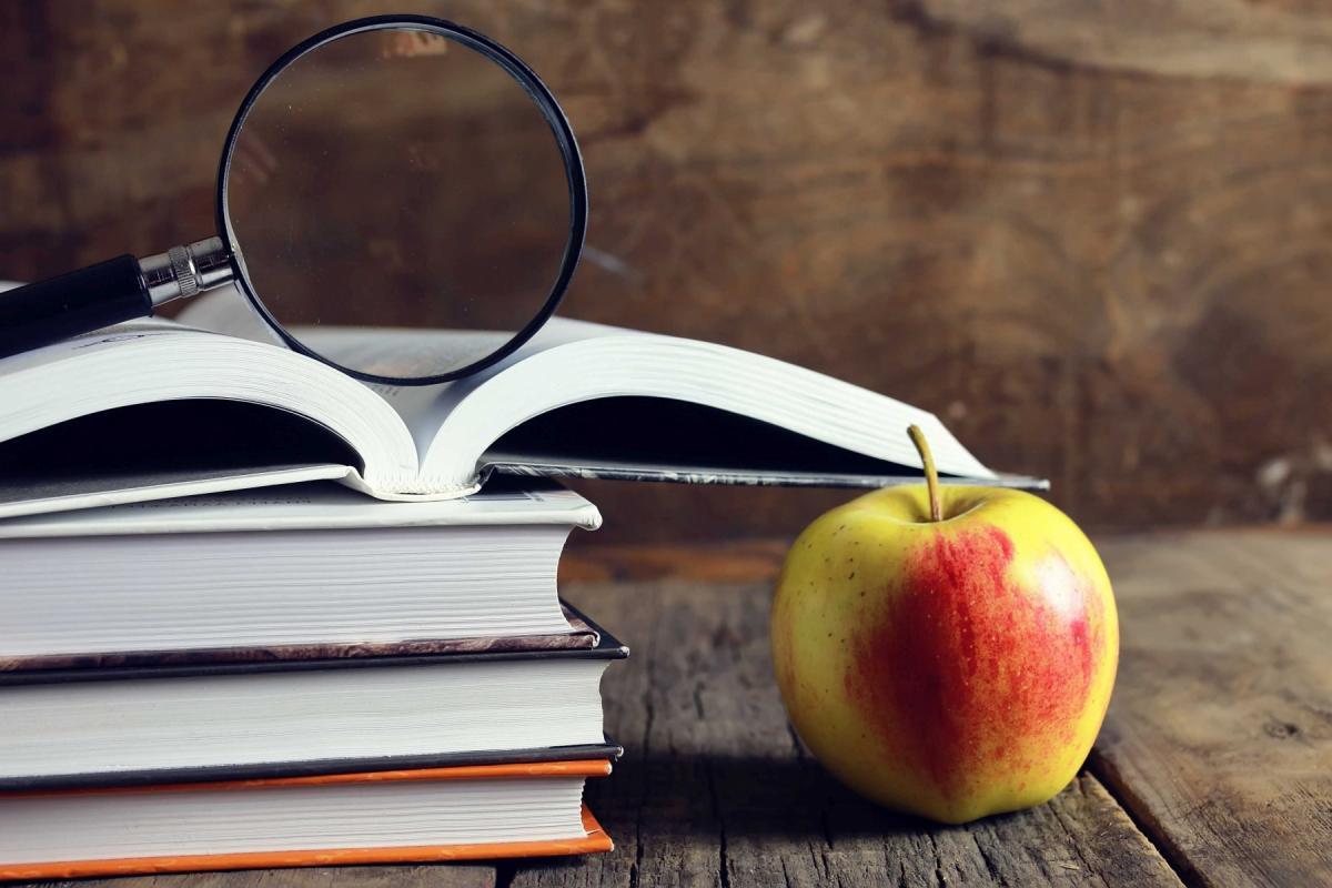 Na drewnianym blacie leżą grube książki, a na nich szkło powiększające. Obol leży jabłko.