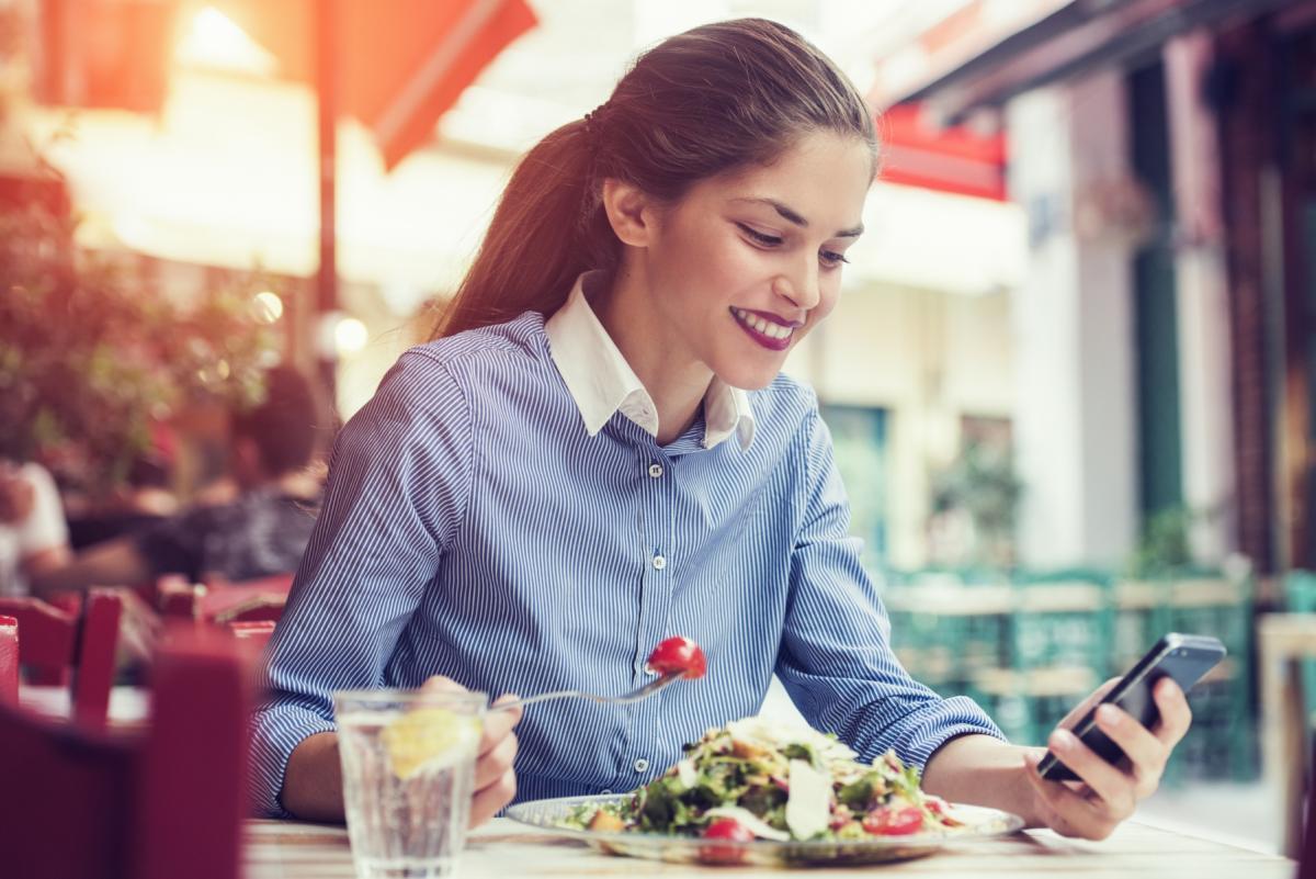 Ładna kobieta siedzi przy stole i je sałatkę. Sprawdza coś w telefonie.
