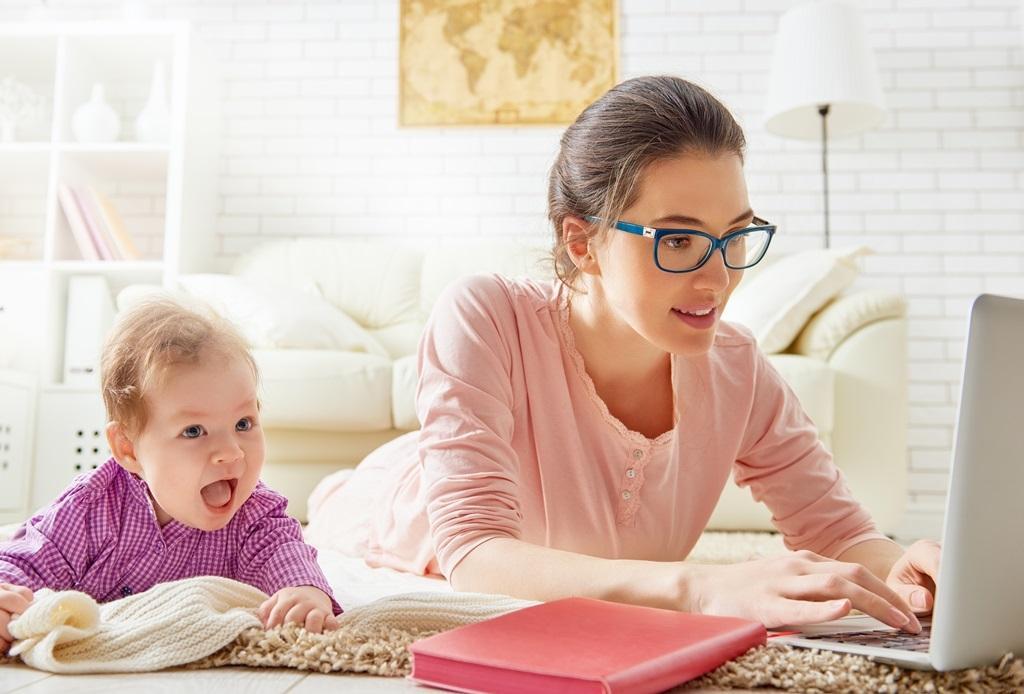 Mama siedzi przy laptopie z dzieckiem