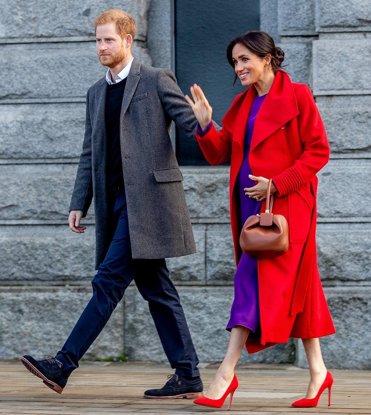 Ciężarna księżna Meghan w fioletowej sukni i czerwonym płaszczu
