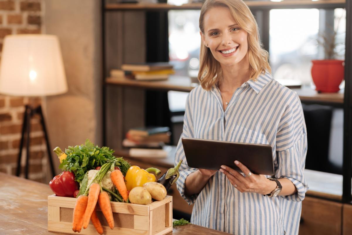 Młoda kobieta w kuchni trzyma tablet. Obok, na blacie leży skrzynka z warzywami.