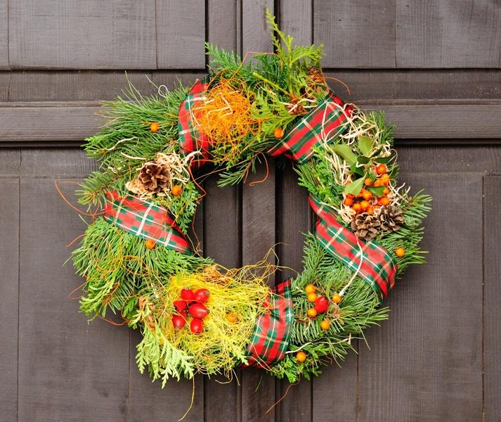 Świąteczna ozdoba na drzwiach z kraciastą wstążką