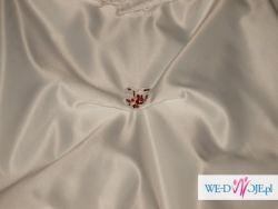 Piękna biała suknia z rubinowymi zdobieniami.