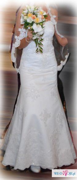 Piękna śnieżnobiała suknia ślubna z koronką.