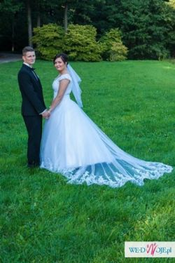 Piękna suknia ślubna wiązana z podpinanym koronkowym trenem