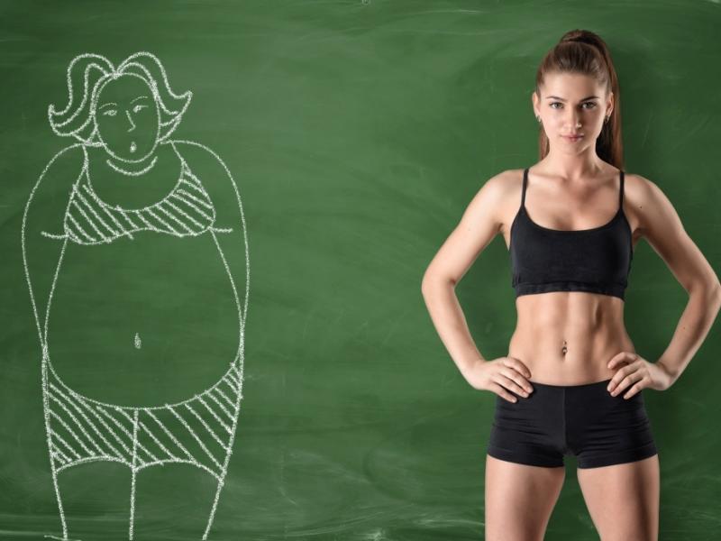 Zgrabna kobieta na tle tablicy. Na tablicy narysowany kredą wizerunek otyłej kobiety.