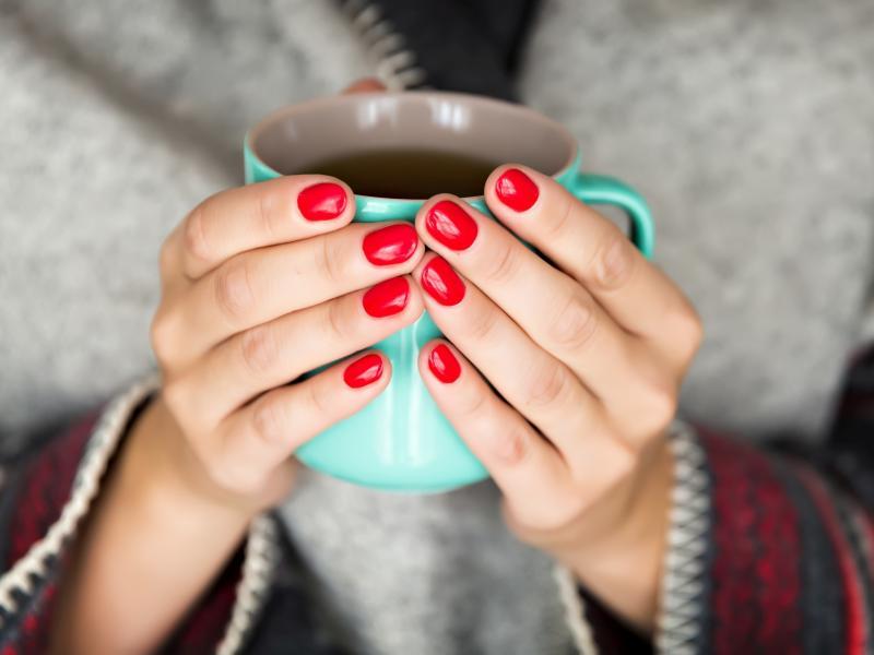 Kobiece dłonie z paznokciami pomalowanymi na czerwono trzymają kubek z herbatą