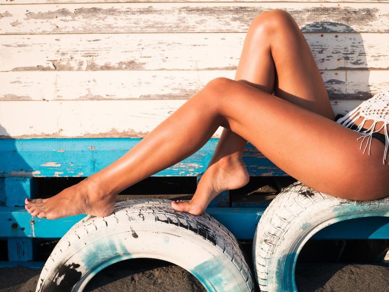 Zbliżenie na zgrabne, opalone nogi kobiety w bikini, bez opuchlizny.