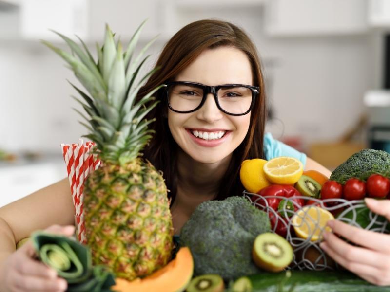 Młoda uśmiechnięta kobieta w kuchni otoczona świeżymi warzywami i owocami.