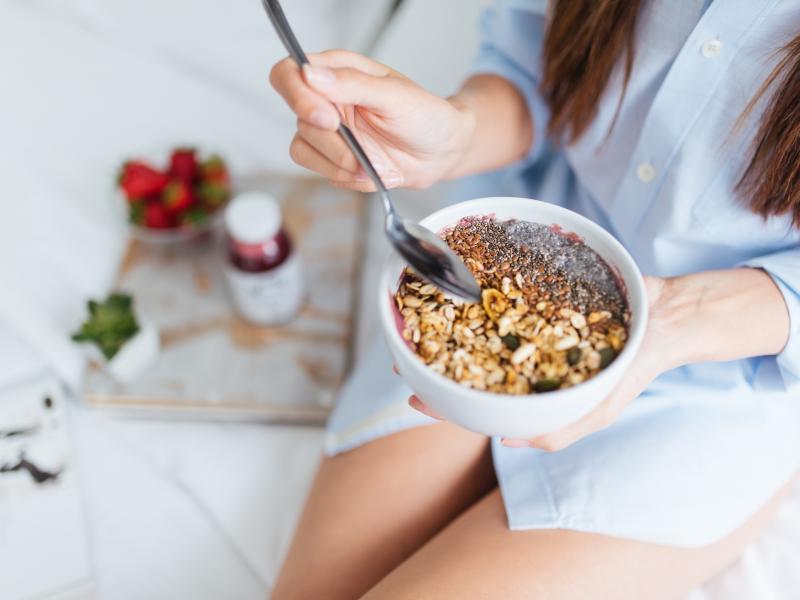 Kobieta w niebieskiej, męskiej koszuli trzymająca miseczkę ze śniadaniem. Zbliżenie na miskę z płatkami i orzechami.