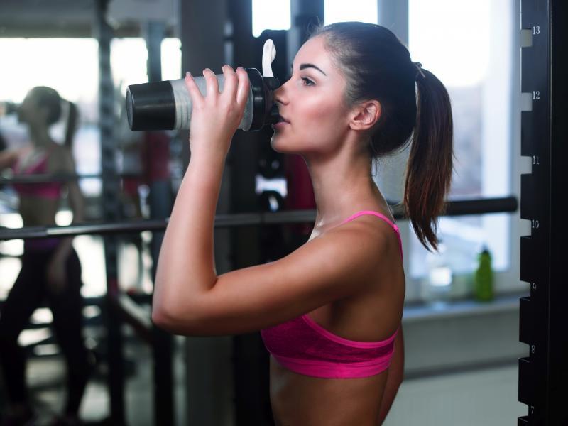 Młoda, zgrabna kobieta pije odżywkę białkową na siłowni.
