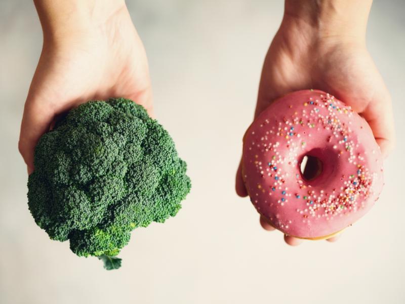 Dłonie trzymające donut i brokuł