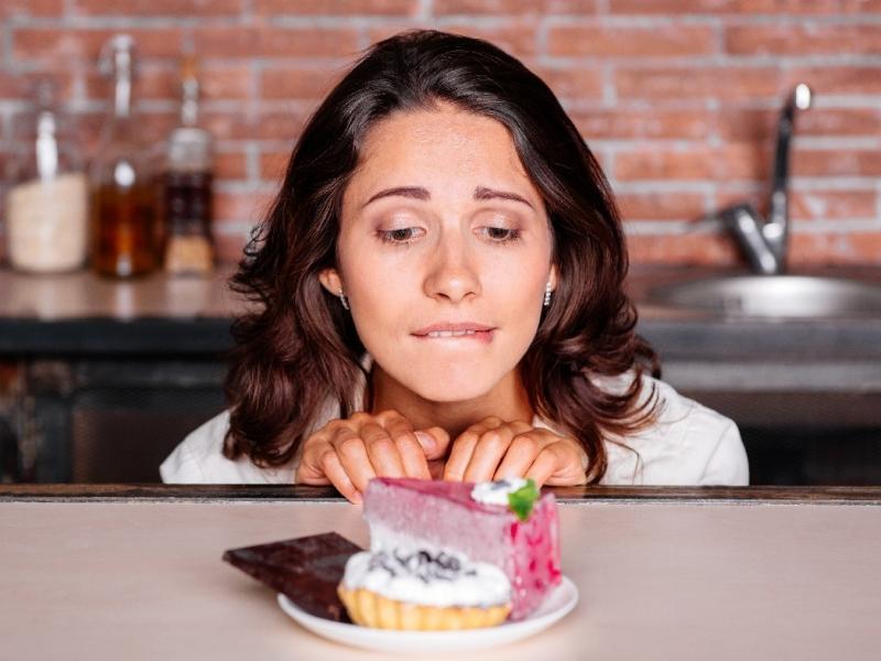 Kobieta na diecie, patrzy tęsknie na ciastka