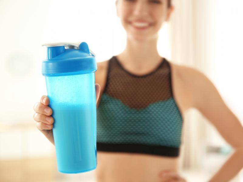 Młoda kobieta pije odżywkę białkową