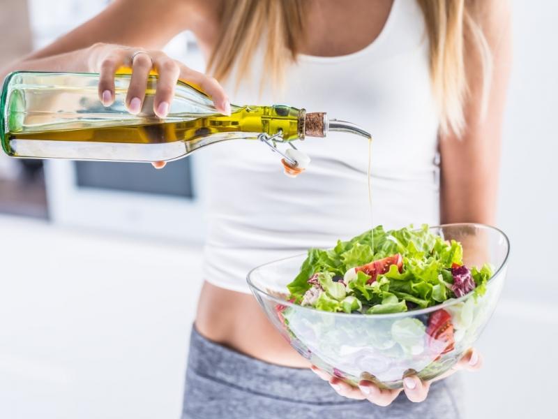 Kobieta stosuje dietę śródziemnomorską. Przygotowuje sałatkę z oliwą z oliwek.