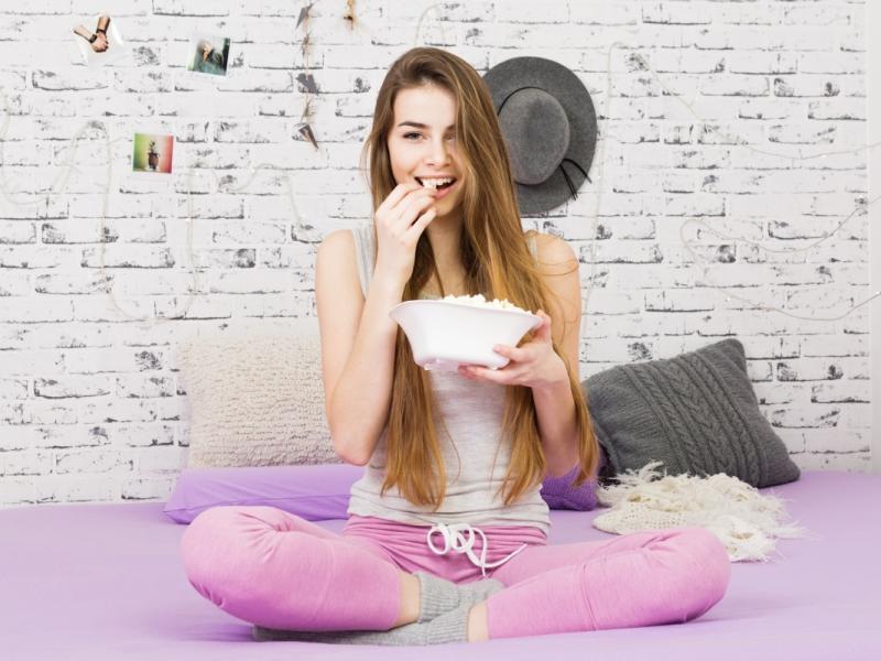 Młoda kobieta  ubrana w dresy siedzi na łóżku i je popcorn.