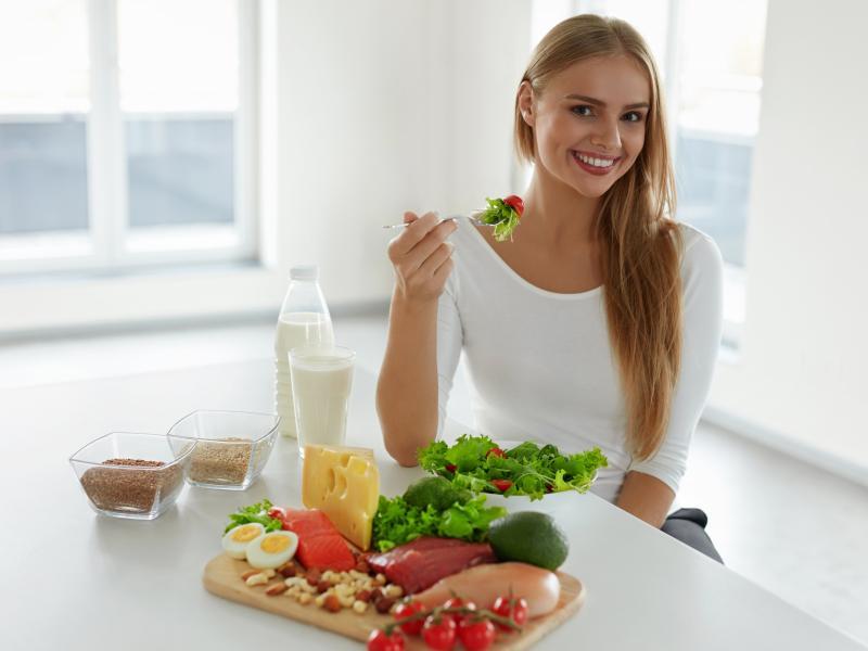 Kobieta jedząca sałatkę. Na stole produkty wysokobiałkowe: nabiał, jajka, mięso