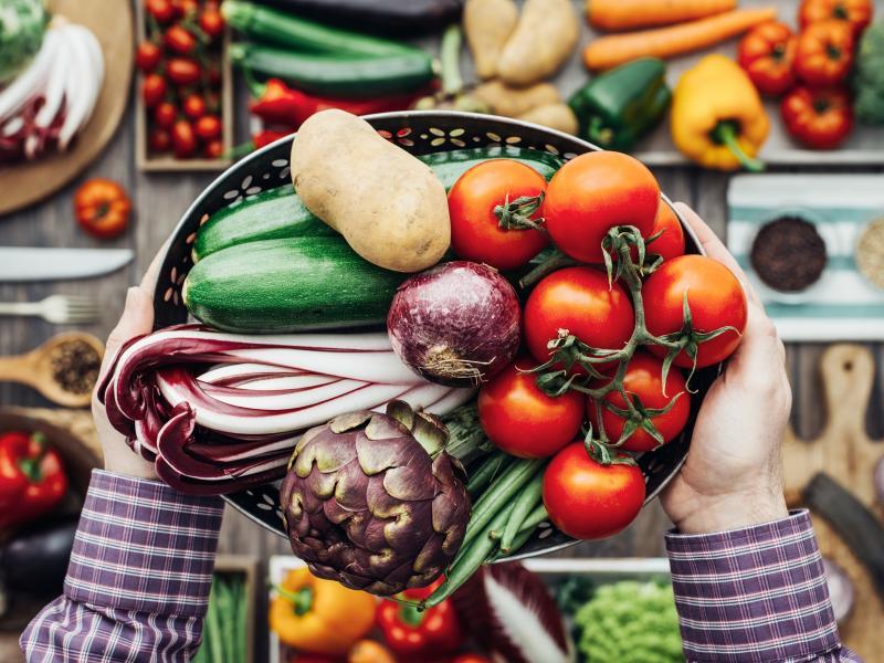 Świeże warzywa w durszlaku trzymane w dłoniach mężczyzny. Inne warzywa w tle.