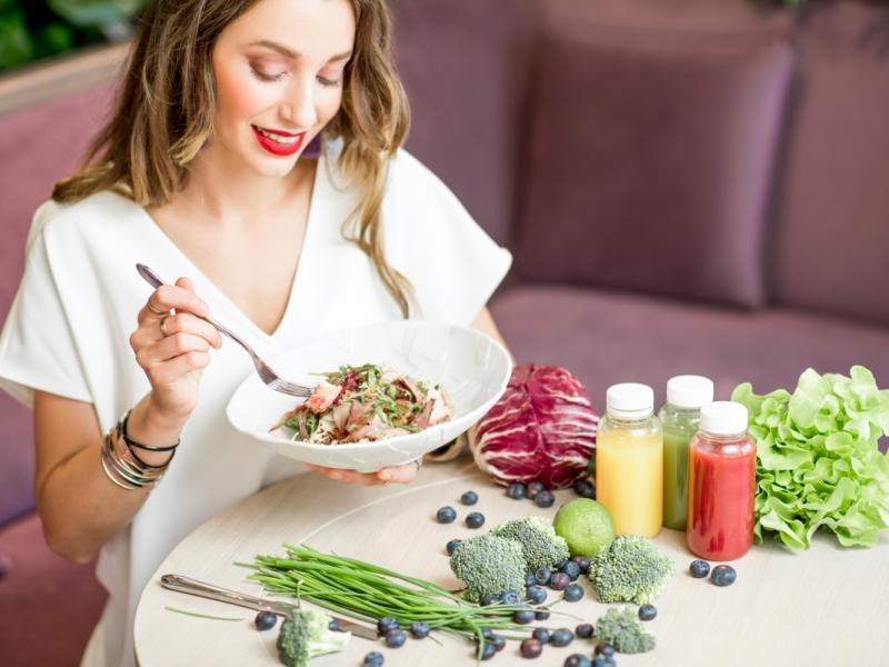 Kobieta na diecie je sałatkę. Obok na stole leżą soki, owoce i warzywa.