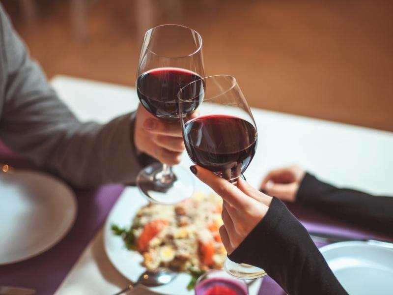 Zbliżenie na kobiecą i męską dłoń, które trzymają kieliszki z czerwonym winem.