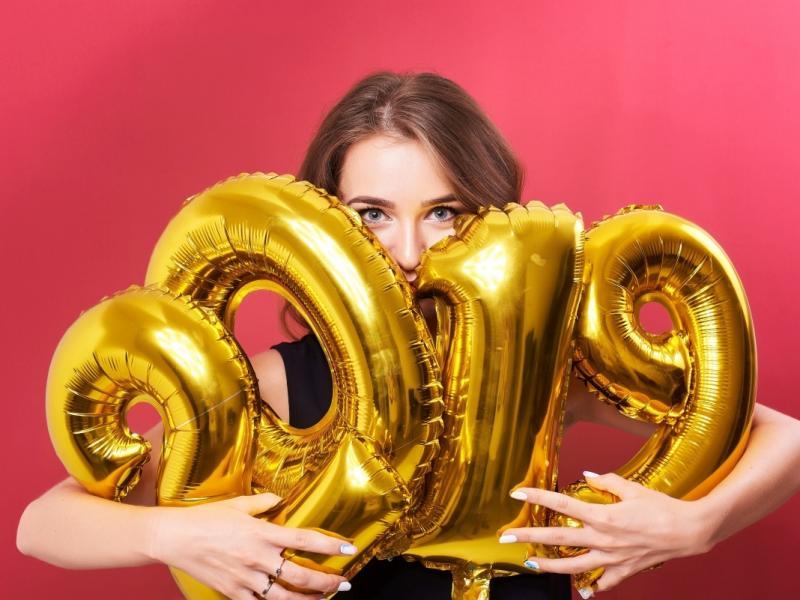 Postanowienia noworoczne na rok 2019. Młoda kobieta trzyma duże balony układające się w cyfrę 2019