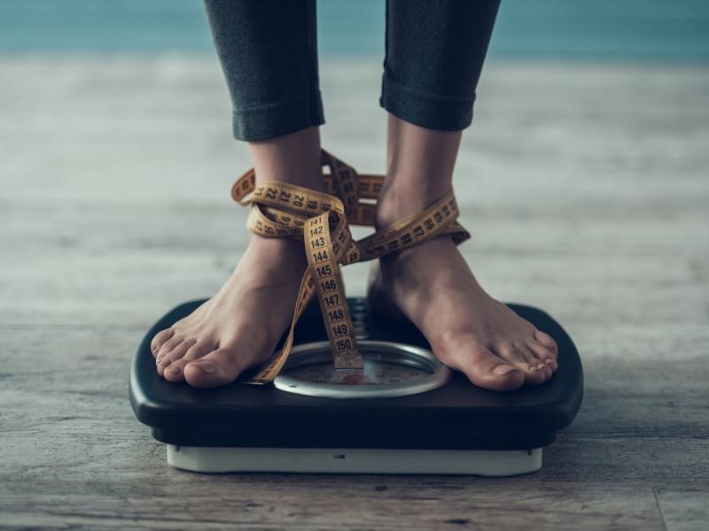 Kobieta widzi spadek masy ciała na wadze, efekt diety dr Dąbrowskiej,