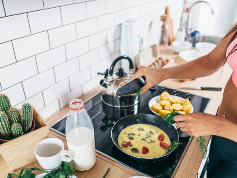 Kobieta gotuje omlet bogaty w białko z warzywami.
