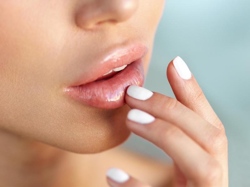 Kobieta smaruje usta balsamem