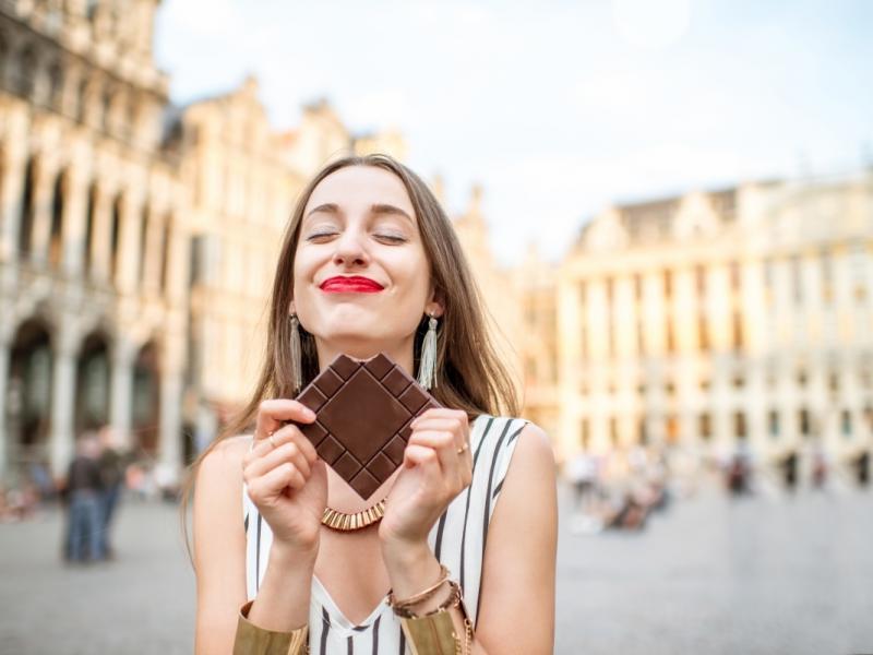 Młoda kobieta je czekoladę na placu w zabytkowym mieście.