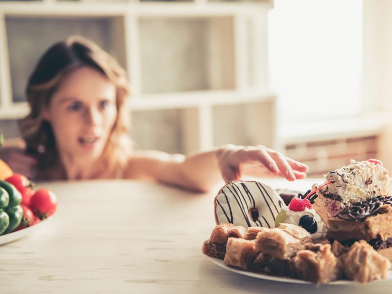 Kobieta sięga po słodycze, źródło węglowodanów prostych!