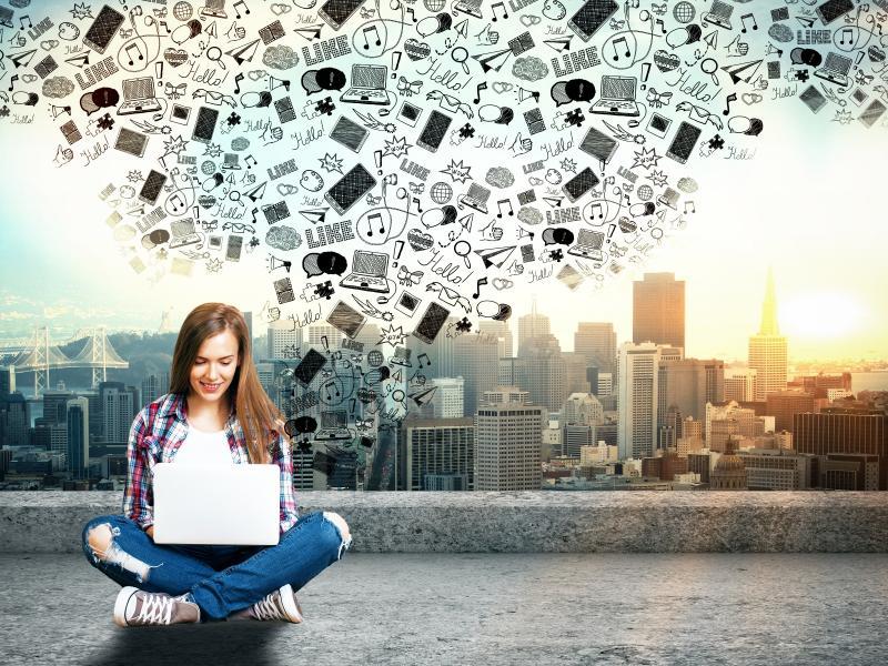Młoda kobieta z laptopem na kolanach na dachu budynku. Na laptopem chmurka z ikonami z social media. W tle duże miasto.