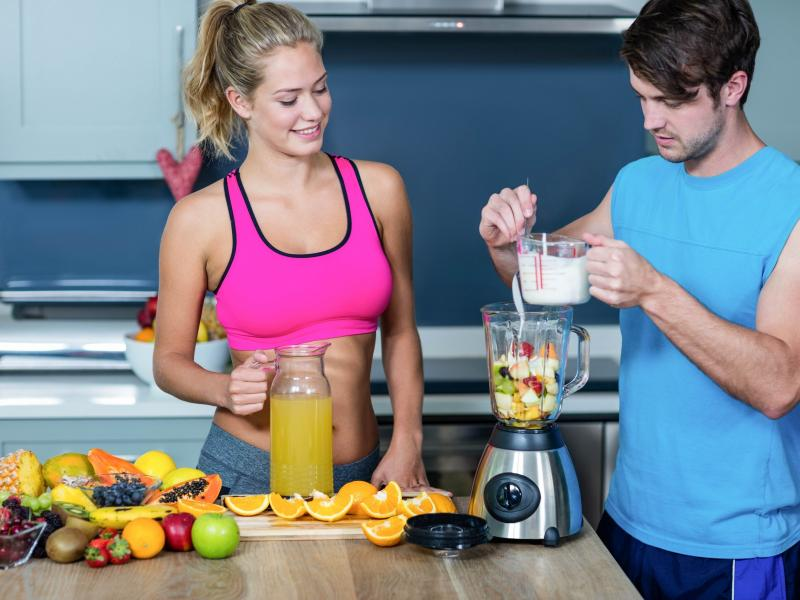 Młoda para przygotowująca koktajl owocowy w kuchni.