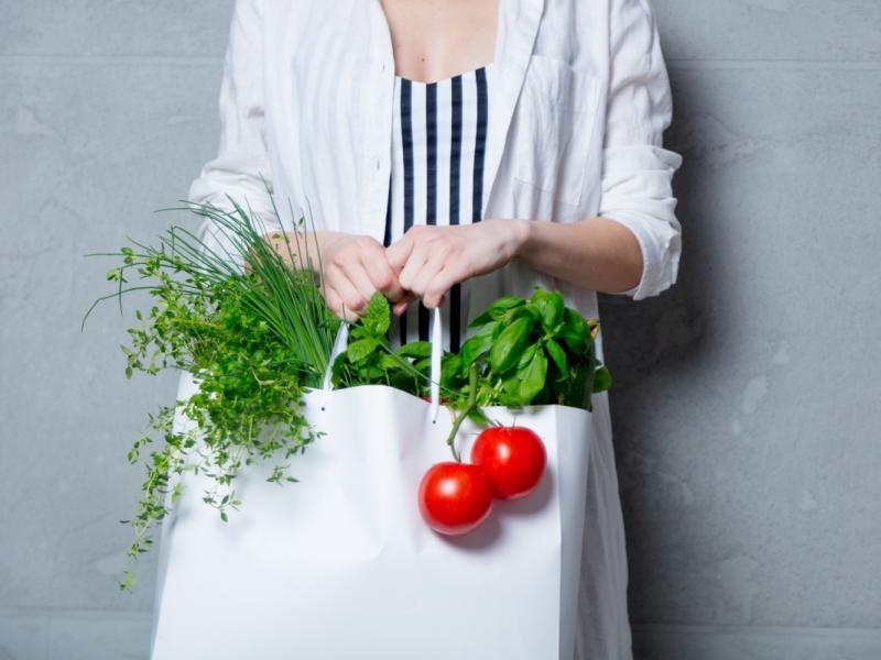 Kobieta trzyma torbę ze świeżymi warzywami. Peganizm