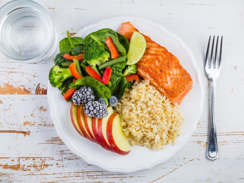 Na białym talerzu zdrowy posiłek kasza, warzywa, łosoś, jabłka i owoce leśne.