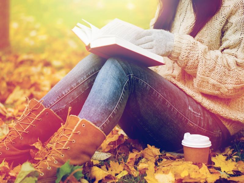 Kobieta siedząca na jesiennych liściach, z książką i kawą.