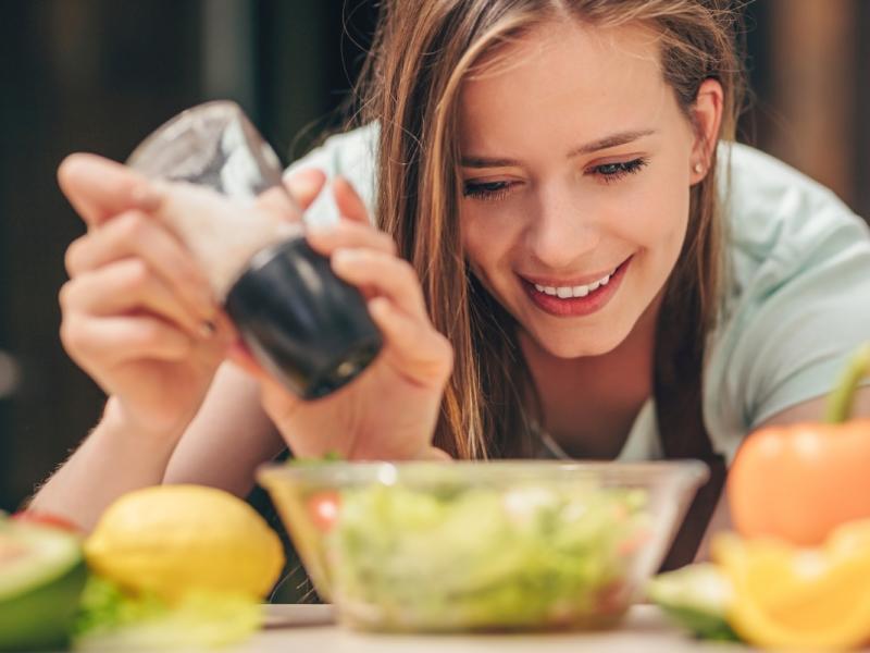 Zbliżenie na twarz młodej kobiety, która soli sałatkę warzywną.