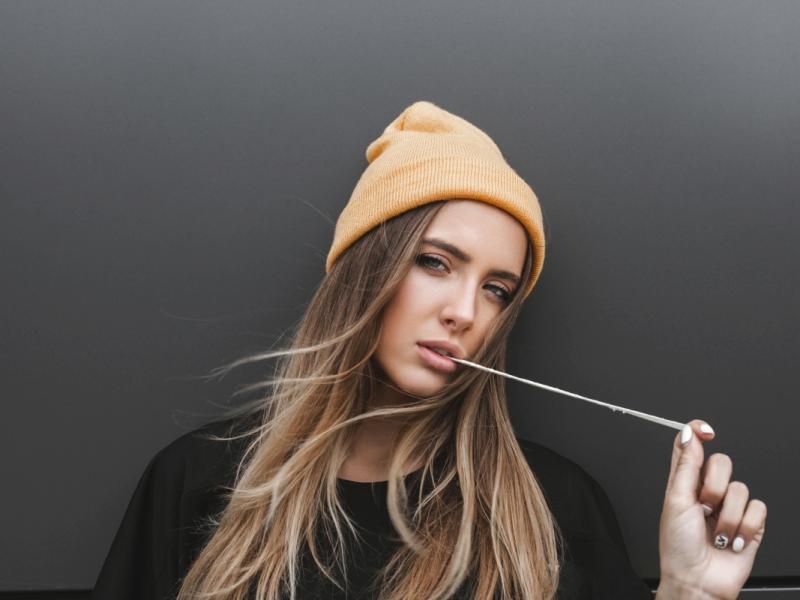 Młoda kobieta w czapce żuje gumę.