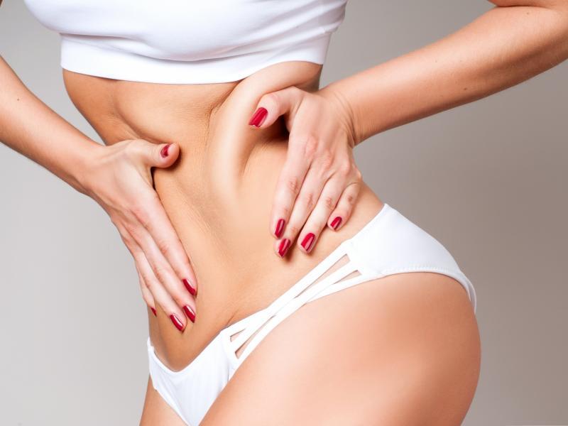 Zbliżenie na brzuch szczupłej kobiety w białej bieliźnie. Kobieta łapie się za tkankę tłuszczową.