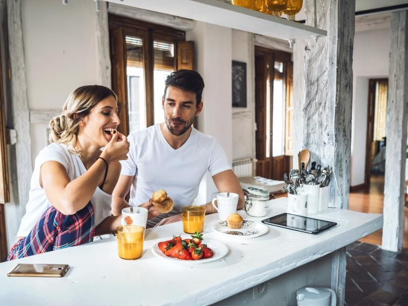 Młoda para jedząca śniadanie w kuchni.
