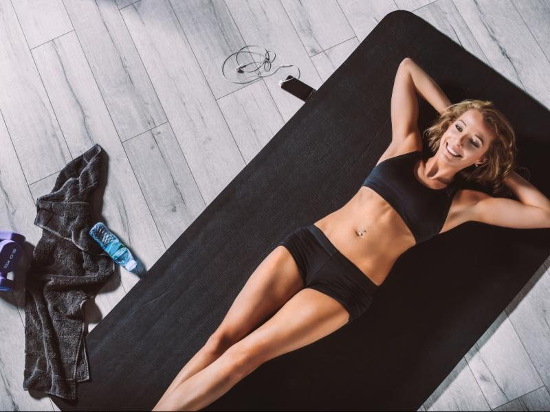 Młoda, zgrabna kobieta w stroju sportowym leży na macie od ćwiczeń.