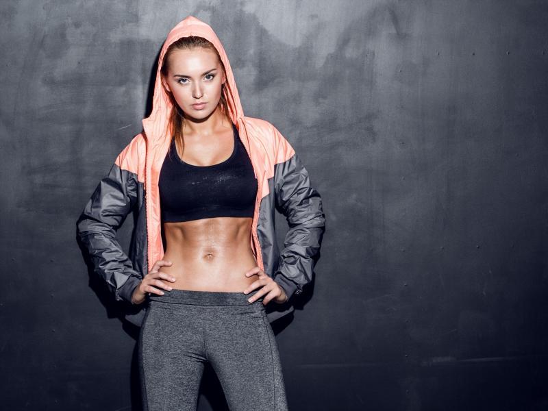 Fit kobieta w stroju sportowym z odsłoniętym brzuchem.
