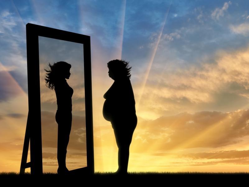 Grafika. W lustrze przegląda się otyła kobieta, w odbiciu widzi szczupłą wersję siebie.