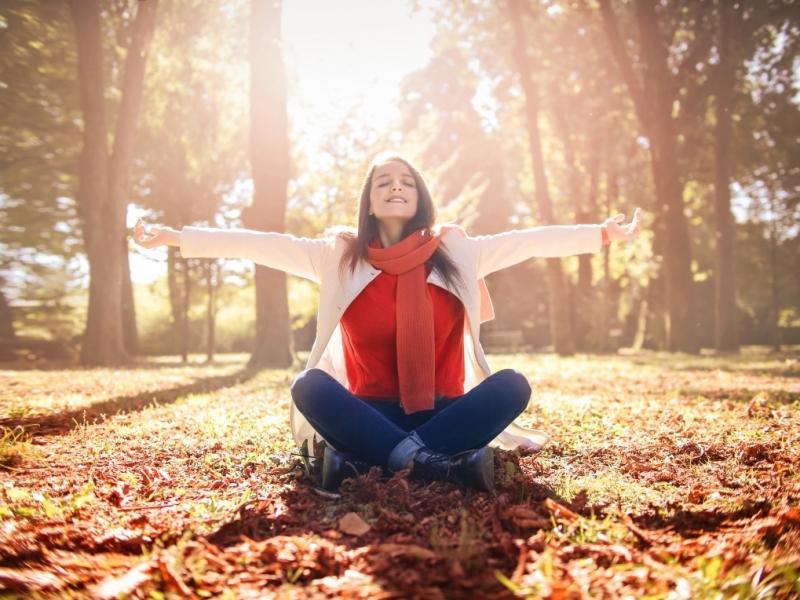 Młoda kobieta w swetrze siedzi na jesiennych liściach.